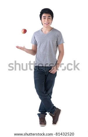 A happy young asian man casting an apple - stock photo