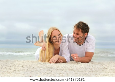A happy, young attractive married couple in love are laying in the white sand on the beach by the ocean while on summer vacation. - stock photo