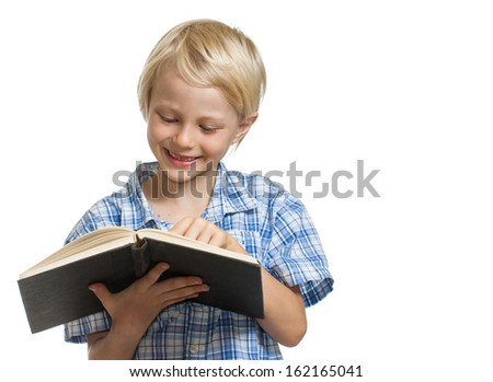 A happy young boy holding and reading a thick book. Isolated on white.