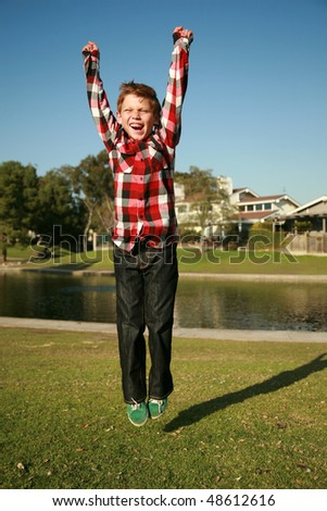 a happy young boy jumps in the air - stock photo