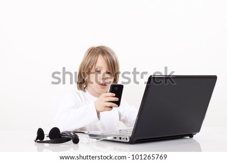 A happy young boy looks something on the Internet - stock photo