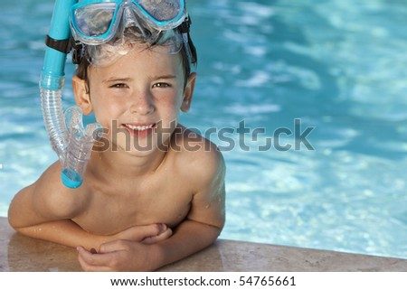 A happy young boy relaxing on the side of a swimming pool wearing blue goggles and snorkel - stock photo