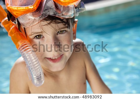 A happy young boy relaxing on the side of a swimming pool wearing orange goggles and snorkel - stock photo
