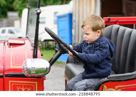 A happy young boy sits in an old shiny vintage red fire truck holding on to the steering wheel pretending to drive.  - stock photo