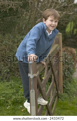 A happy young boy standing on a five bar gate