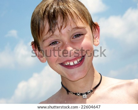 a happy young boy wet from swimming - stock photo