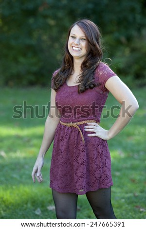 A happy young brunette girl posing outdoors with a green background on a sunny day. - stock photo