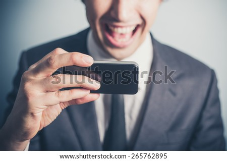 A happy young businessman is using his smartphone - stock photo
