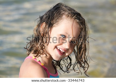 a happy young caucasian child with blue eyes and a gorgeous smile and sand in her wet hair