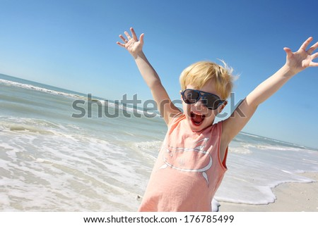 a happy young child is smiling big and raising his arms over his head in joy on vacation at the beach by the ocean shore. - stock photo