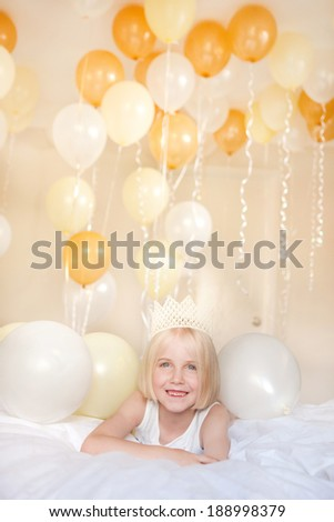 A happy young child is surrounded by white and yellow helium balloons.  Could represent party, fun, celebration - stock photo