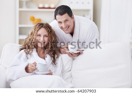 A happy young couple in dressing gowns at home