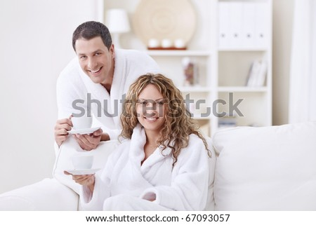 A happy young couple in dressing gowns at home - stock photo