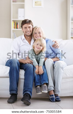A happy young couple on the couch at home - stock photo