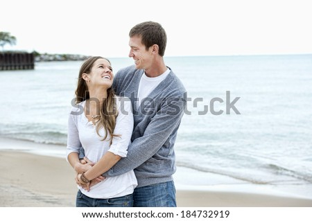 A happy young couple walking on the beach on a sunny day while looking into each others eyes with the water in the background and wearing casual lifestyle clothing. - stock photo