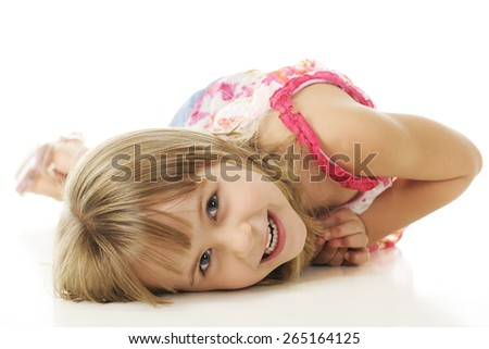 A happy young elementary girl curling herself backwards while laying on the floor.  On a white background.