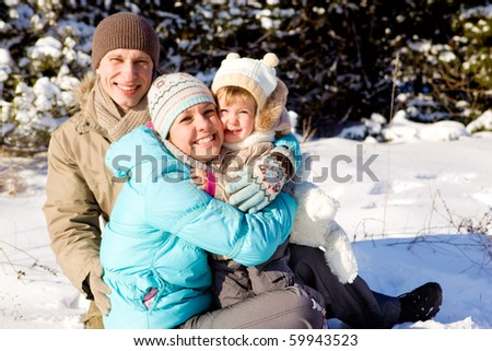 A happy young family hugging - stock photo