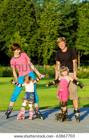 A happy young family in roller skates - stock photo