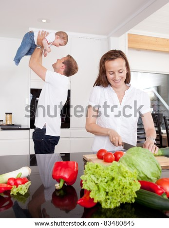 A happy young family in the kitchen, mother preparing food and father playing with son