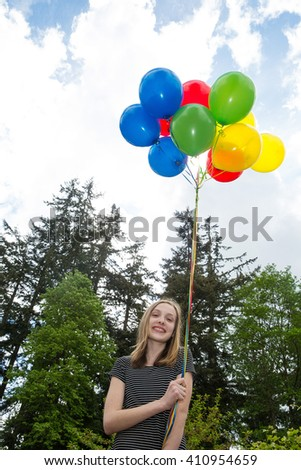 A happy young girl holding a cluster of colorful balloons - stock photo
