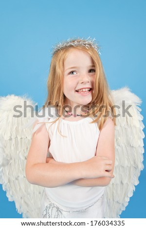 A happy young girl in an angel costume. - stock photo
