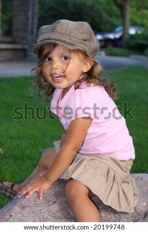 A happy young girl playing outside climbing on a rock