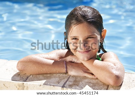 A happy young girl relaxing on the side of a swimming pool and smiling - stock photo