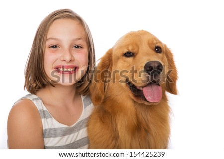 A happy young girl sits with her beautiful golden retriever dog