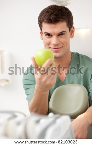 A happy young male dentist holding an apple.  Shallow depth of field, focus on dentist.
