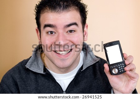 A happy young man showing the screen of a smartphone.  The white cell phone screen includes the clipping path. - stock photo