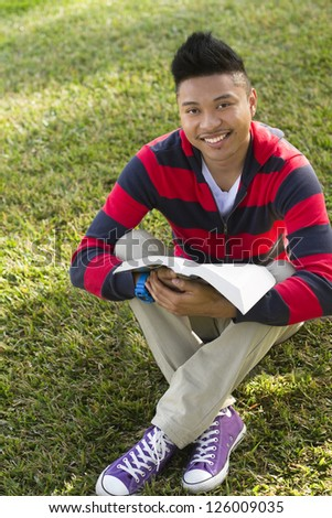 A happy young man sitting on a lawn with a book. - stock photo