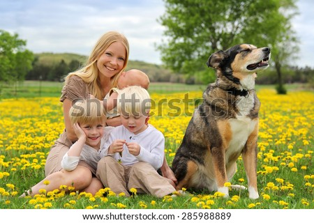 A happy young mother and her three children, a newborn baby girl, a toddler boy and big brother are playing in a country flower meadow with their pet dog on a spring day. - stock photo