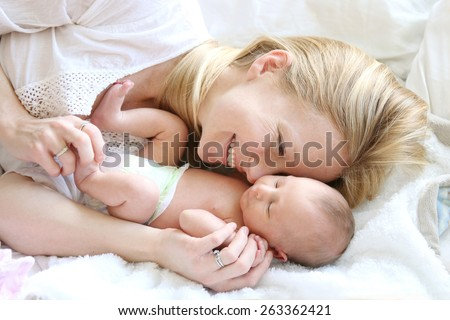 A happy young mother is laying in her white bed, lovingly hugging and snuggling her newborn baby daughter. - stock photo