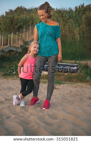 A happy young mother wearing fitness gear is looking down lovingly at her daughter, who is leaning against her mother, smiling and relaxed. Both are wearing fitness gear and are on the beach.