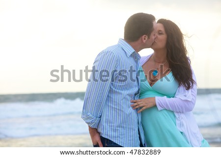 A happy young pregnant couple in love on the beach - stock photo