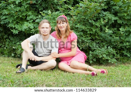 a happy young pregnant woman with her husband resting in a park