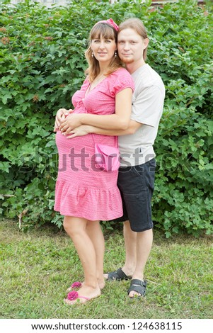 a happy young pregnant woman with her husband rests in a park - stock photo