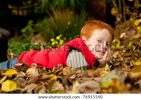 A happy young red haired boy is lying in a pile of colorful autumn / fall leaves in a garden or park setting, with chin resting on hand and smiling - stock photo