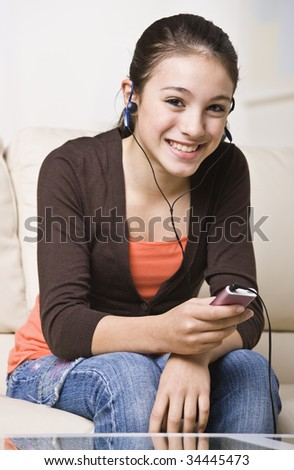 A happy young teenager listening to an MP3 music player.  She is smiling at the camera.  Vertically framed shot. - stock photo