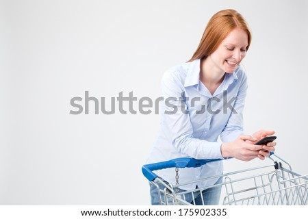 A happy young woman checking a groceries shopping list on her phone and leaning on a shopping cart. - stock photo