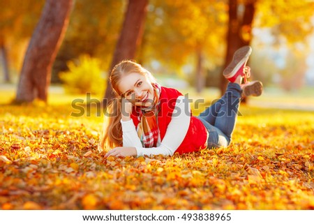 a happy young woman resting outdoors in autumn