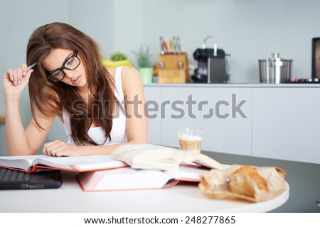 a happy young woman studying in kitchen - stock photo