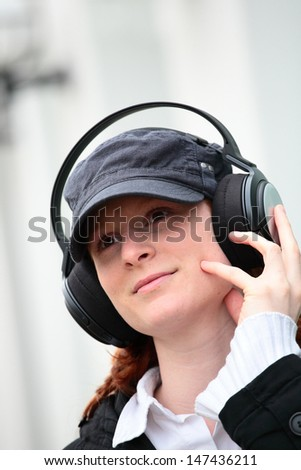 A happy young woman with a baseball cap and large headphones listening to music.