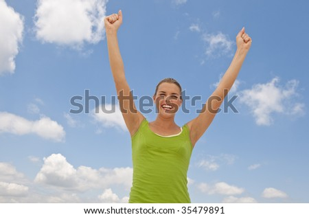 A happy young woman with her arms stretched up toward the blue sky and clouds.  She is smiling. Horizontally framed shot.