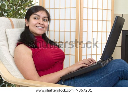 A happy young woman working on her laptop from home. - stock photo