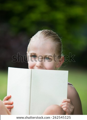 A happy young 7 year old girl with blond hair and blue eyes is looking over a white book outdoors.  She is studying or reading a novel.