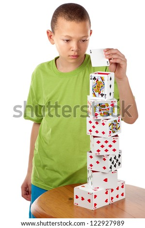 A hard concentrating boy completes his playing card tower project by placing the last card on top of it. - stock photo