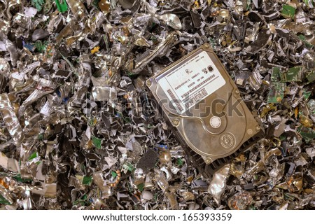 A hard drive resting on a pile of shredded hard drives - stock photo