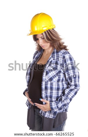 a hard working woman who is pregnant holding her belly feeling her baby kick while she looks at her stomach.