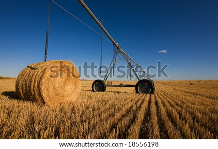 A harvested wheat field with a pivot and bales - stock photo